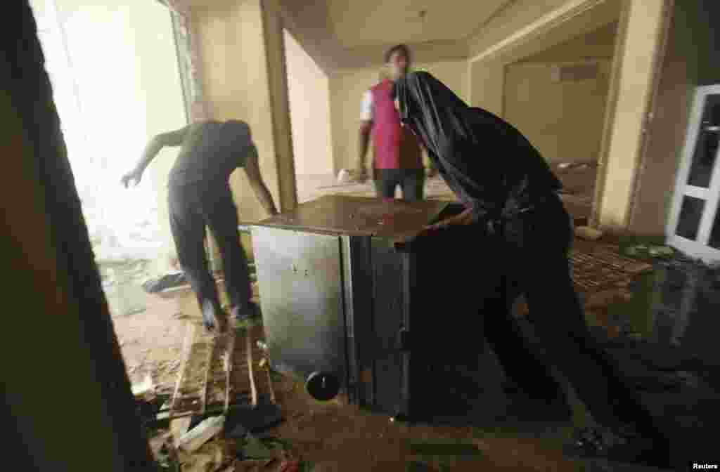 Looters push part of a cooking stove out of the Muslim Brotherhood's headquarters after it was burned down by protesters opposing Egyptian President Mohamed Mursi in Cairo's Moqattam district July 1, 2013.