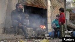 Người đàn ông và các con ngồi bên đống lửa trong khu vực bị vây hãm của thành phố Homs