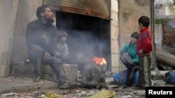A man and children sit around a fire in the besieged area of Homs, Jan. 30, 2014.