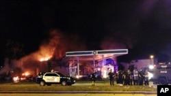 密尔沃基市警察在燃烧的加油站旁边(2016年8月13日)