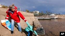 志願者梅瑞迪斯和她七歲的兒子從洛杉磯附近的聖莫妮卡海灘收撿塑料瓶(資料照)