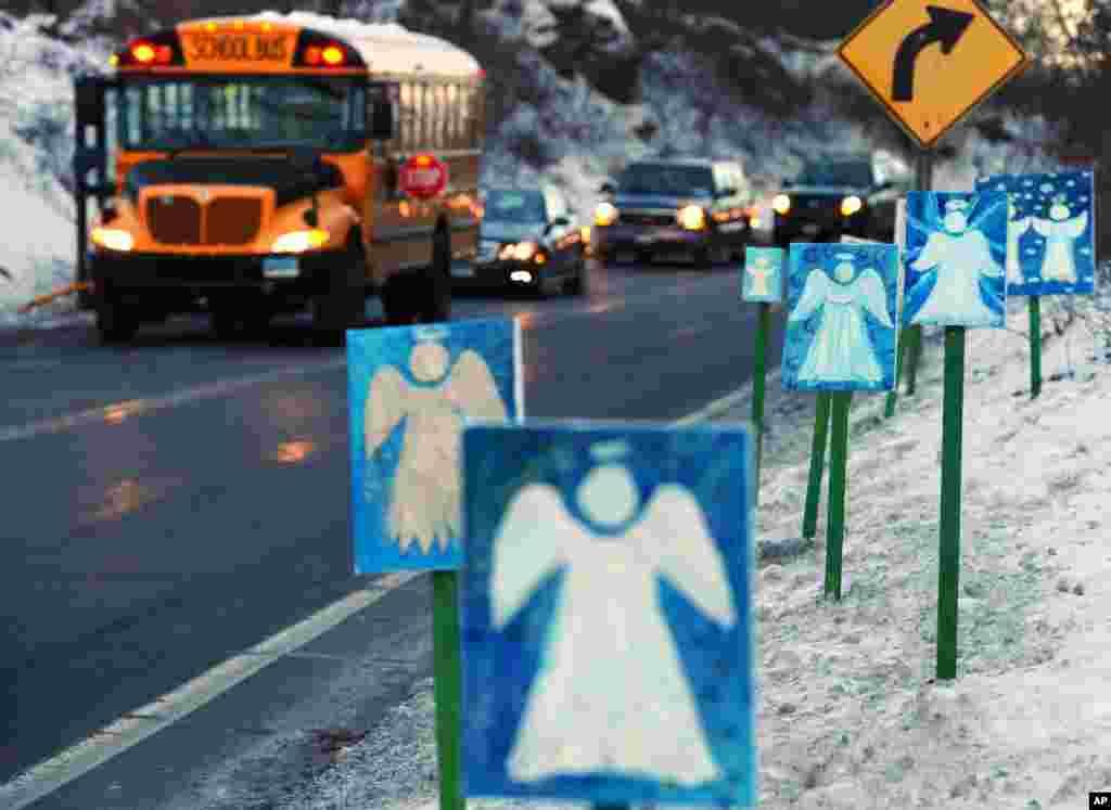 미국 최악의 총기참사로 27명의 학생과 교직원이 숨진 코네티컷주 샌디훅 초등학교가 사건 3주만에 수업을 재개한 가운데, 학생들을 태우고 새 교사로 향하는 등교 버스. 거리에 희생자들을 상징하는 26개의 천사그림이 걸려있다.