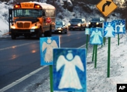 FILE - A bus traveling from Newtown, Connecticut, to Monroe stops in front of 26 angels along the roadside on the first day of classes for Sandy Hook Elementary School students since the December 14 shooting.