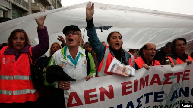 Protesters hold a plastic sheet to protect themselves from the rain as they take part in an anti-austerity rally during a 24-hour general labour strike in Athens November 6, 2013. Thousands of striking Greek workers marched to parliament in pouring rain o