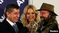 Circus owner Jaromir Joo, right, holds tiger cub as he congratulates Andrej Babis, leader of ANO movement, Prague, Oct. 26, 2013.
