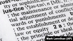 "In this December 12, 2018, photo, ""justice"" is shown in a Merriam-Webster dictionary in New York. (AP Photo/Mark Lennihan)"