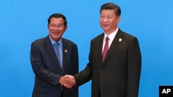 Cambodian Prime Minister Hun Sen, left, and Chinese President Xi Jinping, right, shake hands during the welcome ceremony for the Belt and Road Forum, at the International Conference Center at Yanqi Lake in Beijing, Monday, May 15, 2017. (Roman Pilipey/Pool Photo via AP)