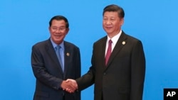 Cambodian Prime Minister Hun Sen, left, and Chinese President Xi Jinping, right, shake hands during the welcome ceremony for the Belt and Road Forum, at the International Conference Center at Yanqi Lake in Beijing, Monday, May 15, 2017.