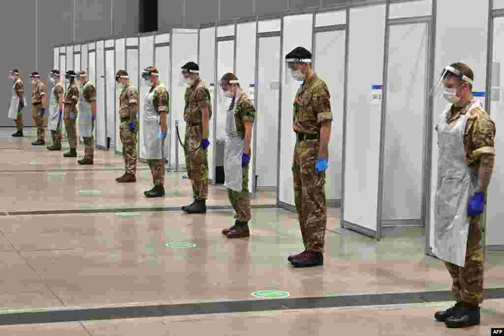 Soldiers observe a 2-minute silence for Armistice day in remembrance of the nations war dead at a coronavirus rapid testing center in Liverpool, northwest England.