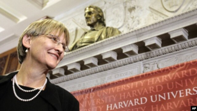 Harvard University President Drew Gilpin Faust stands beneath a bust of the founder of the university, John Harvard