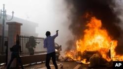 Mobil dibakar di luar gedung parlemen di tengah kerusuhan di Ouagadougou, Burkina Faso, Kamis (30/10). (AP/Theo Renaut)