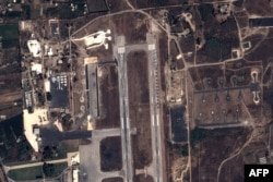 FILE - This handout image taken by EADS' Astrium Press on September 20, 2015, by Pleiades Satellite purports to show a view of Russian fighter jets and helicopters at a military base in Latakia, Syria.