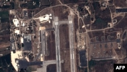FILE - This handout image taken by EADS' Astrium Press on Sept. 20, 2015, by Pleiades Satellite purports to show a view of Russian fighter jets and helicopters at a military base in Latakia, Syria.