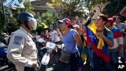 People chant anti-government slogans as police block their access to downtown Caracas, Venezuela, Jan. 24, 2015.