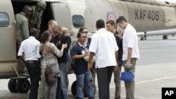 Des travailleurs humanitaires de la Norwegian Refugee Council (NRC) après leur libération, sont accueillis par leurs collègues à leur descente d'un hélicoptère à l'aéroport Wilson du Kenya Air Force, à Nairobi, 2 juillet 2012.