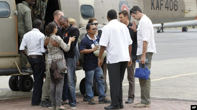 Released foreign aid workers from the Norwegian Refugee Council are welcomed by their colleagues upon arriving at the Wilson airport in Nairobi, July 2, 2012.