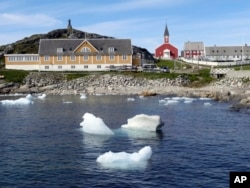 In this image taken on June 13, 2019 small pieces of ice float in the water off the shore in Nuuk, Greenland.