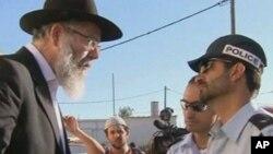 Polisi Israel (kanan) memberitahu warga di permukiman Migron bahwa mereka harus meninggalkan permukiman ilegal tersebut paling lambat hari Selasa (4/9).