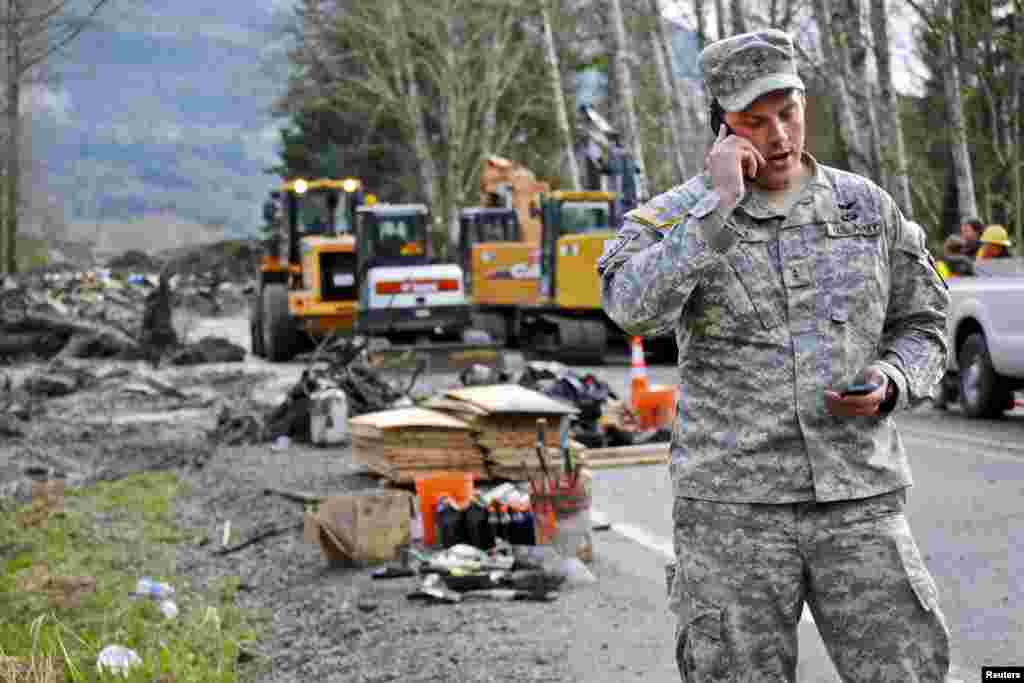Chief Warrant Officer Kevin Crisp, liaison officer for the Washington National Guard, coordinates the arrival of a search team at the site of the mudslide in Oso, Washington, March 26, 2014.