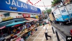A tourist walks past Malaysia's famous eatery street, Jalan Alor, a popular tourist spot in Kuala Lumpur, Malaysia on Friday, Sept. 25, 2015.