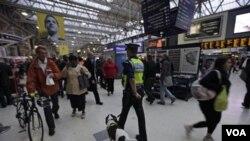 Seorang polisi Inggris dengan anjingnya berpatroli di stasiun kereta kota London.