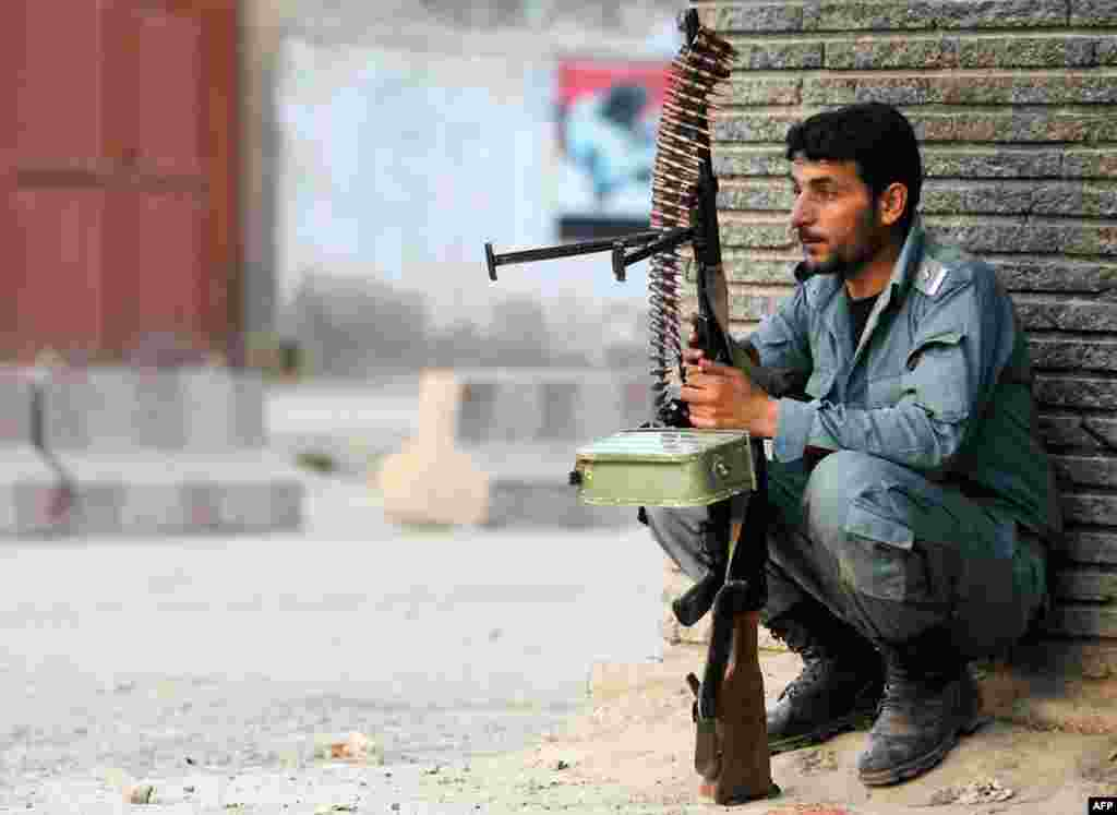 An Afghan policeman keeps guard at the site of an attack in Kabul April 15, 2012. (Reuters)