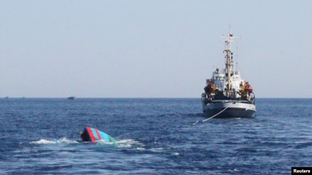 FILE - A Vietnamese sinking boat (L) which was rammed and then sunk by Chinese vessels near disputed Paracels Islands, is seen near a Marine Guard ship (R) at Ly Son island of Vietnam's central Quang Ngai province.