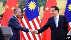 馬來西亞總理馬哈蒂爾和中國總理李克強在人民大會堂舉行記者會後握手。 (2018年8月20日)