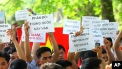 """越南人在河内中国大使馆前示威,手持标语:""""制止中国侵占越南土地"""""""
