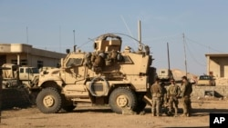U.S. Army soldiers stand outside their armored vehicle on a joint base with Iraqi army south of Mosul, Iraq, Feb. 23, 2017. The new defense spending bill includes money for training to fight ISIS.