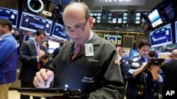 Trader Andrew Silverman (c) works on the floor of the New York Stock Exchange, Dec. 2, 2015.