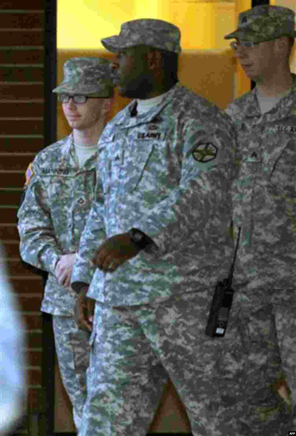 Army Pfc. Bradley Manning, left, is escorted out of a courthouse at Fort Meade, Md., Friday, Dec. 16, 2011, after the first day of a military hearing that will determine if he should face court-martial for his alleged role in the WikiLeaks classified leak
