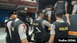 Polisi bersenjata lengkap di depan lokasi penggeledahan tempat kerja terduga teroris yang ditangkap densus antiteror di Sukoharjo akhir Mei lalu. (Foto dok: VOA/Yudha)