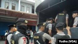 Polisi bersenjata lengkap di depan lokasi penggeledahan tempat kerja terduga teroris yang ditangkap Densus Anti-teror di Sukoharjo (Foto: VOA/Yudha)