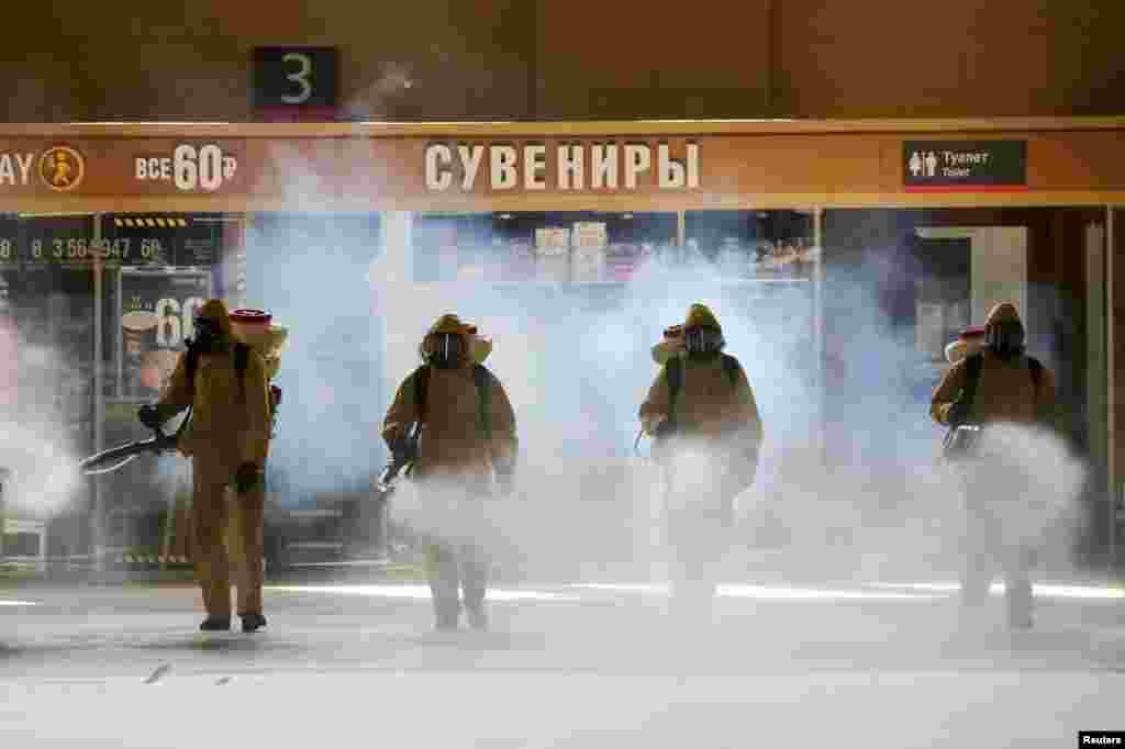 Russia's Emergencies Ministry members wearing personal protective equipment (PPE) spray disinfectant near a gift kiosk at the Kievsky Railway Station amid the outbreak of the coronavirus disease (COVID-19) in Moscow. (Credit: Sandurskaya/Moscow News Agency/Handout)