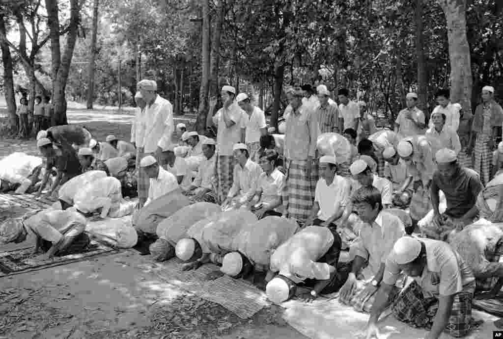 Cambodian Muslim men give thanks to Allah for deliverance in Aranyaprathet, Eastern Thailand on April 25, 1975, after fleeing across the border from Cambodia. Muslim refugees, members of the Cham Ethnic Minority, told newsmen about 30 of their number were killed by Khmer Rouge troops before about 400 got through on Thursday. (AP Photo/LAY)
