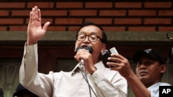 President of National Rescue Party Sam Rainsy, center, gives a speech during a public forum at their party's office in Phnom Penh, Cambodia, July 31, 2013.