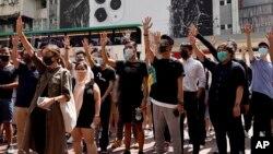 4일 홍콩 도심에서 마스크를 착용한 반정부 시위대가 캐리 람 행정장관 사퇴와 직선제 실시 등을 요구하며 손을 들고 있다.