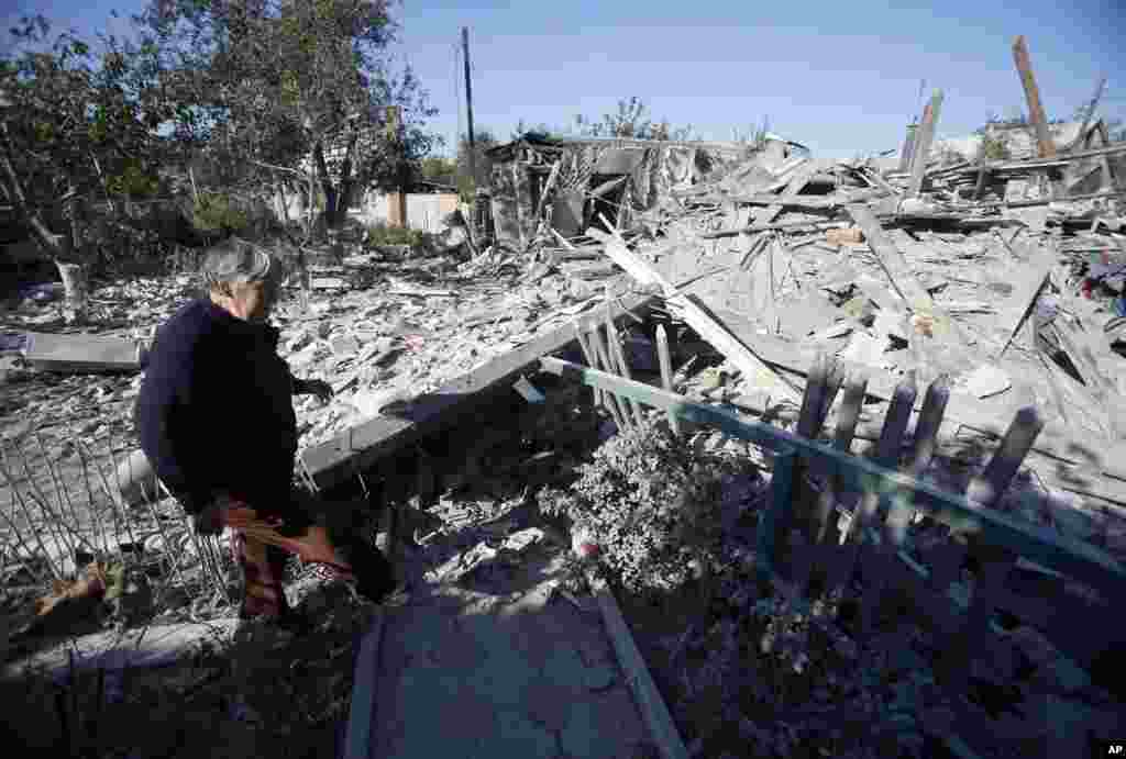 A woman checks damage at a destroyed home after shelling in the city of Donetsk, eastern Ukraine, Sept. 29, 2014.