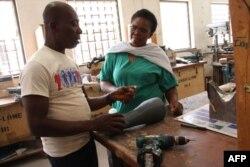 Les orthopédistes togolais font les derniers ajustements au support prothétique imprimé en 3D pour Adjovi Koudahe au CNAO de Lomé, le 19 juin 2018.