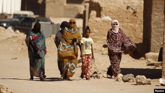 Indigenous Sahrawi women walk through Al Smara desert refugee camp in Tindouf, southern Algeria, March 4, 2016.