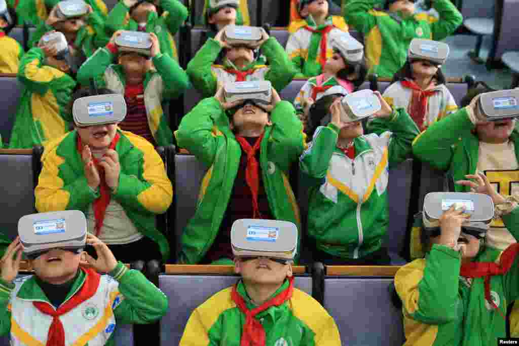 Primary school students wear virtual reality (VR) headsets inside a classroom in Xiangxi Tujia and Miao Autonomous Prefecture, Hunan province, China, March 14, 2018.