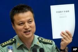 中国国防部发言人杨宇军手持《中国的军事战略》白皮书在新闻发布会上(2015年5月26日)