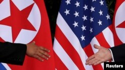 FILE - U.S. President Donald Trump and North Korea's leader Kim Jong Un meet at the start of their summit on the resort island of Sentosa, Singapore, June 12, 2018.