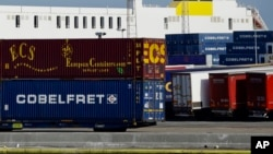 Truck trailers are parked among stacked cargo containers at the Port of Zeebrugge, in Zeebrugge, Belgium, Thursday, Oct. 24, 2019. British police raided two sites in Northern Ireland and questioned a truck driver as they investigate the deaths of…