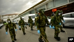 Members of the Military Emergency Unit, walking with special equipment to disinfect areas to prevent the spread of the coronavirus, arrive at Abando train station, in Bilbao, northern Spain, March 23, 2020.