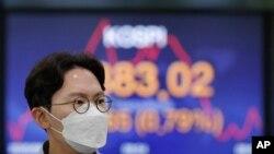 ຜູ້ແລກປ່ຽນອັດຕາເງິນຄົນນຶ່ງຍ່າງຜ່ານ ກະດານດັດຊະນີ Korea Composite Stock Price Index (KOSPI) ທີ່ນະຄອນຫຼວງ ໂໍໍຊລ ເກົາຫຼີໃຕ້.