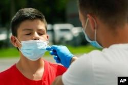 FILE - Agustin Cortez, 13, gets a COVID-19 test, July 15, 2021, in Miami.