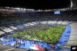 Spectators rush onto the field at Stade de France stadium after an explosion nearby, Nov. 13, 2015.