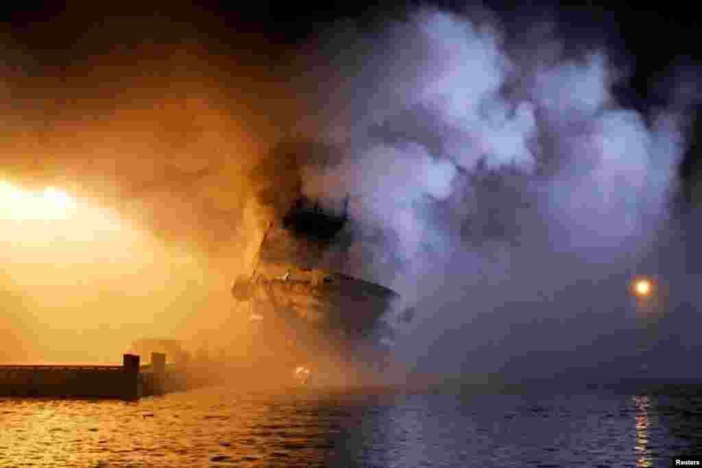 The Russian fishing boat Bukhta Naezdnik burns in the harbor of Tromso, Norway.